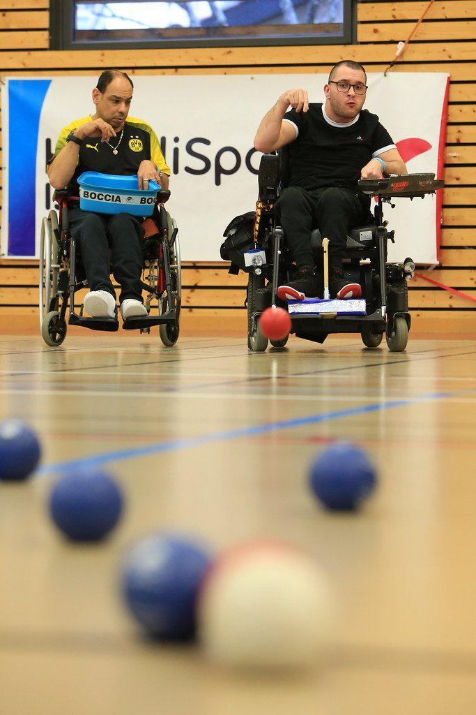 Deux joueurs en situation de handicap moteurs en train de jouer au boccia