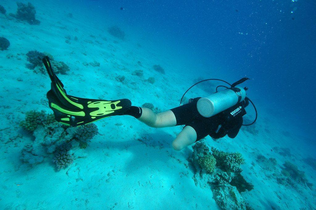 Personne en situation de handicap (unijambiste) en train de faire de la plongée sous marine