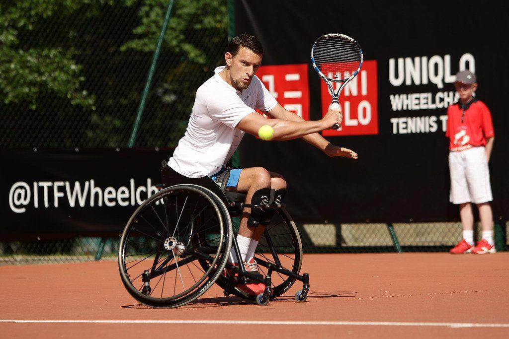 Personne en situation de handicap moteur jouant au tennis adapté